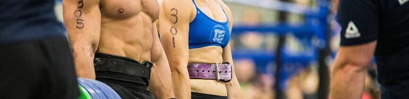 A woman and man at CrossFit games with weights