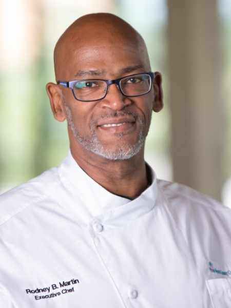 Photo Head shot of our Executive Chef Rodney Martin in a white chef's coat