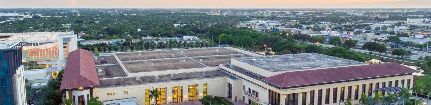 This is a photo of the front of the convention center from an aerial view looking down into the front entry and courtyard with a sunset sky background