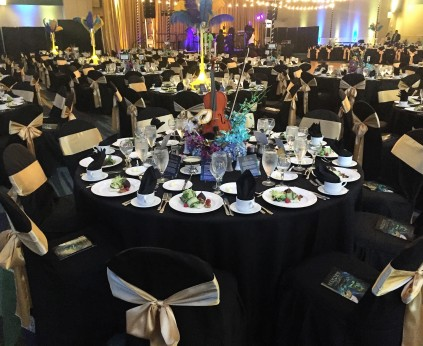 Banquet room set up in all black linens and chair covers with masquerade décor on the tables