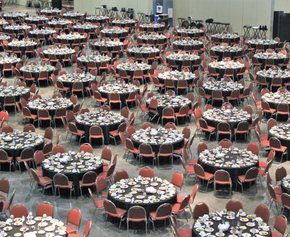 Overhead photo of the exhibit hall set up for a meal function with round tables set up throughout the rooms