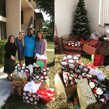 Photo of our team presenting our gifts to the family we were adopting for the holidays. All the gifts are spread out on the grass for the photo