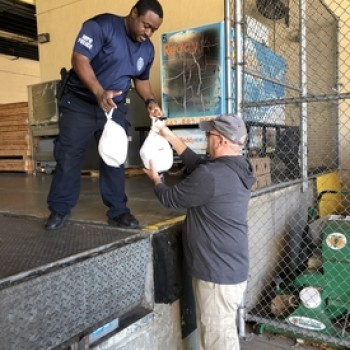 Photo of our staff working with West Palm Police to provide meals to community