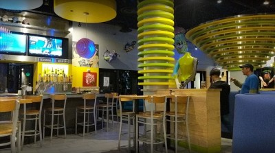 Interior space of bar area of Mellow Mushroom with bright decor